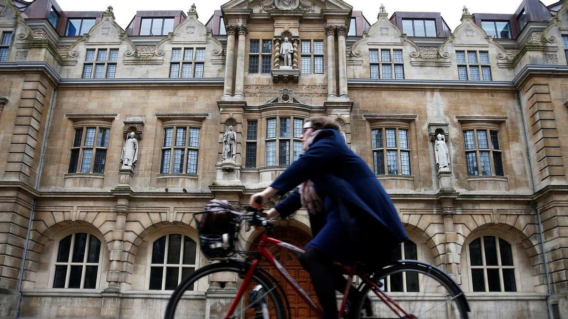 A woman rides a bike next to Oriel College in Oxford, Britain. (Reuters)