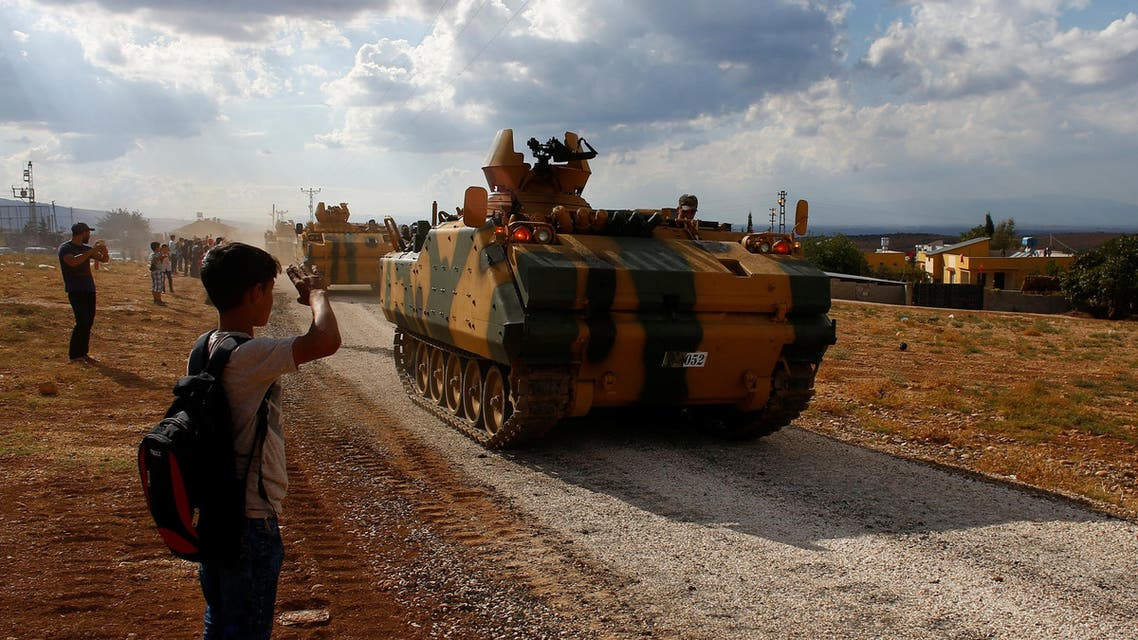 A boy salutes as Turkish army vehicles drive pass by their village on the Turkish-Syrian border line in Reyhanli, Hatay province, Turkey, October 11, 2017. reuters