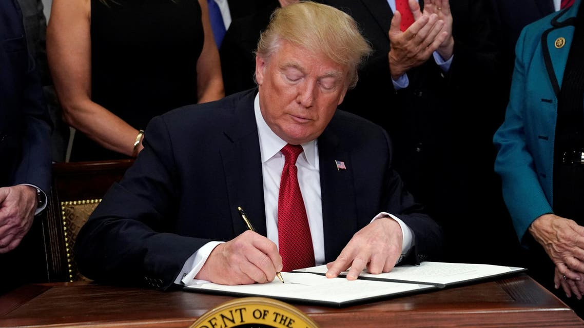 U.S. President Donald Trump signs an executive order to make it easier for Americans to buy bare-bones health insurance plans and circumvent Obamacare rules at the White House in Washington, U.S., October 12, 2017. reuters