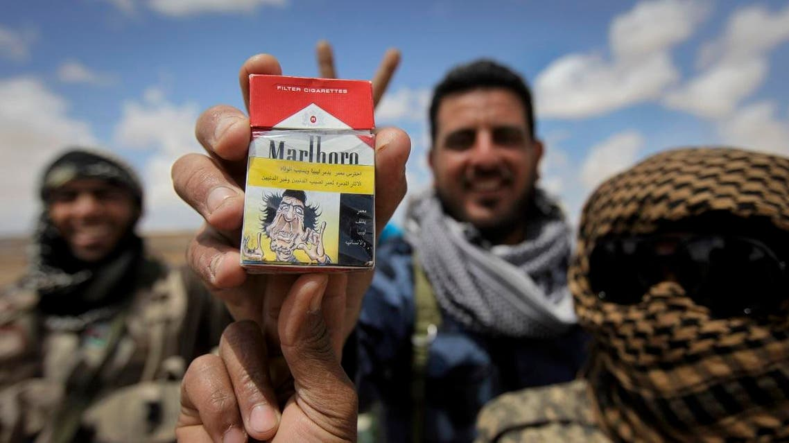 Libyan rebel fighters hold up a packet of cigarettes on which they had put a homemade joke health warning featuring a caricature of Moammar Gadhafi, on the outskirts of Ajdabiya, Libya Monday, April 18, 2011. (AP)
