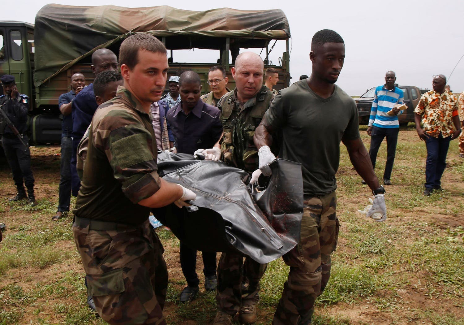 French soldiers and rescuers carry a body after a propeller-engine cargo plane crashed in the sea near the international airport in Ivory Coast's main city, Abidjan. (Reuters)