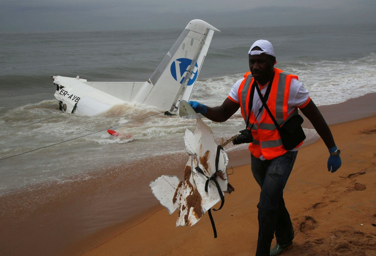 A rescuer carries a piece of a cargo plane after it crashed in the sea near the international airport in Ivory Coast's main city, Abidjan. (Reuters)