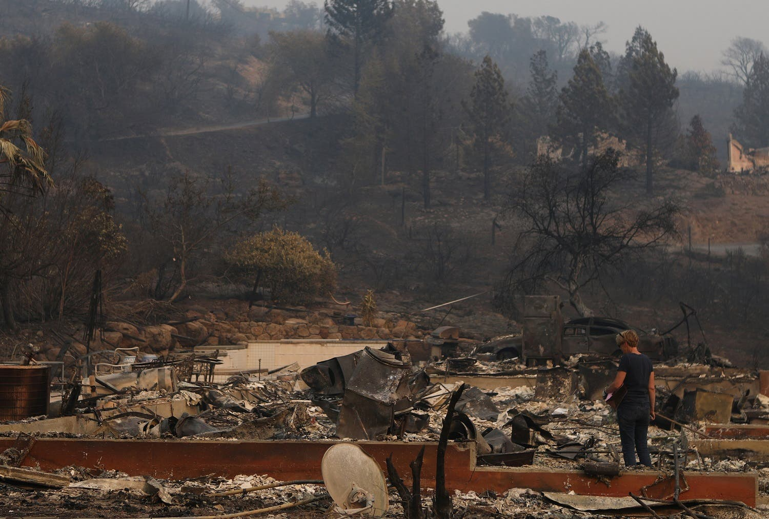 A woman surveys the remains of a home destroyed by wildfire in Napa, California, US, on October 13, 2017. (Reuters)