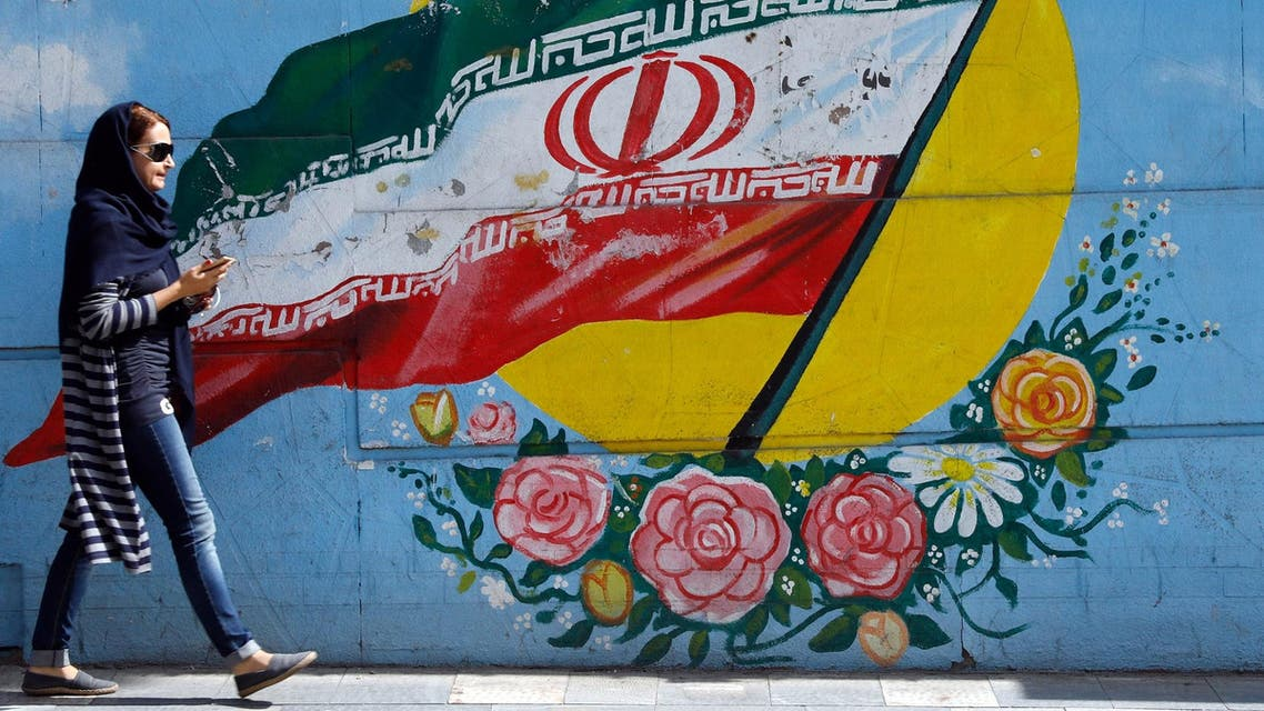 An Iranian woman walks past a mural of the Iranian flag in the capital Tehran, on October 14, 2017. (AFP)