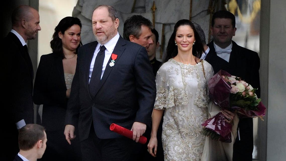 """(FILES) This file photo taken on March 7, 2012 shows US producer Harvey Weinstein (3rdL), leaving the presidential Elysee Palace in Paris with his wife Georgina Chapman, after the French President awarded him with the Legion d'Honneur (Legion of Honor). France will strip disgraced Hollywood movie mogul Harvey Weinstein of the prestigious Legion d'Honneur, President Emmanuel Macron said on October 15, 2017. """"I have taken steps to revoke the Legion d'Honneur (Legion of Honour)"""" from Weinstein -- accused by several women of sexual harassment, groping and rape -- Macron said in a televised interview. (AFP)"""