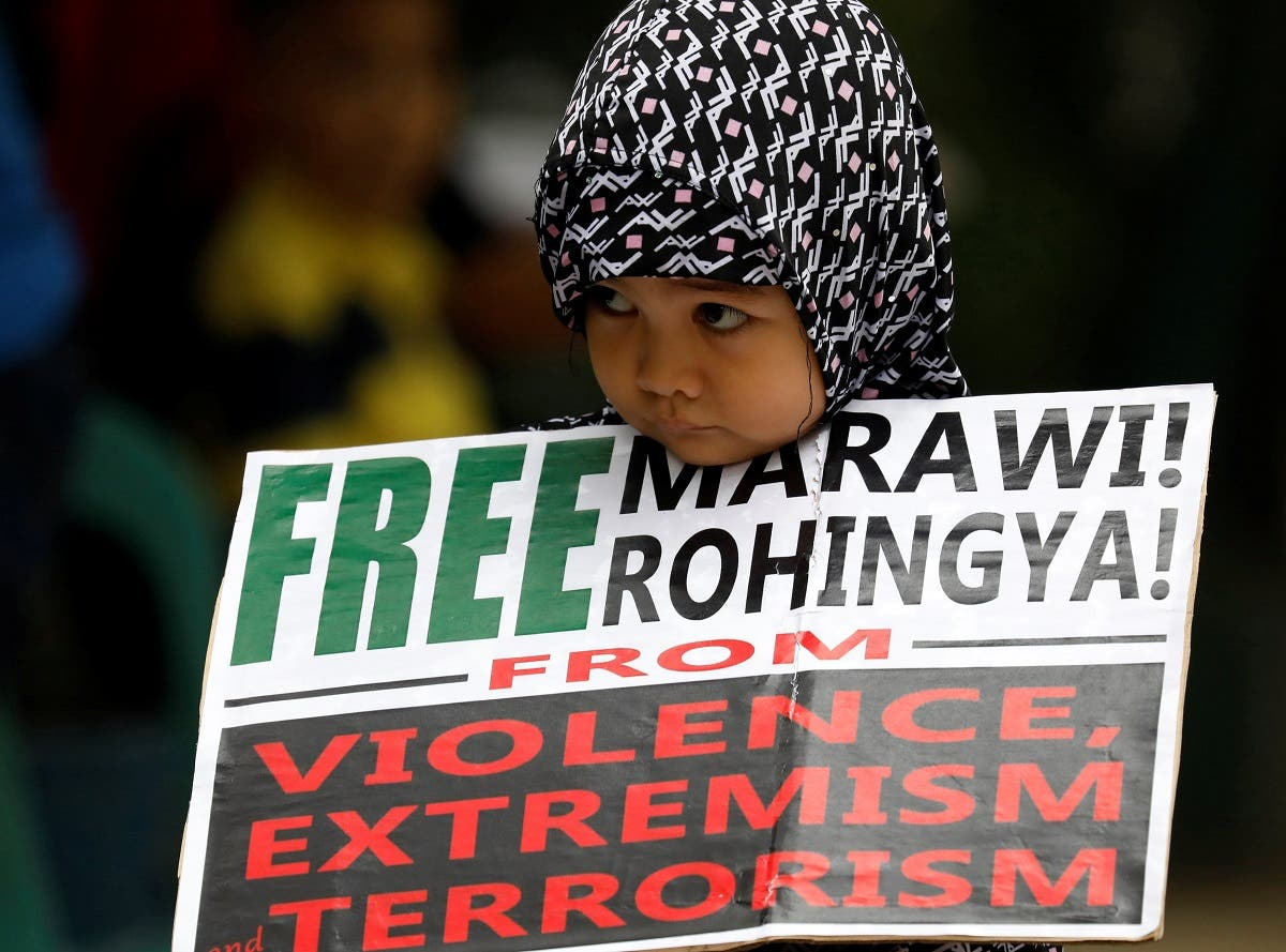 A Muslim young girl holds a placard after noon prayers for the Marawi siege and the plight of the Rohingya in Quezon City, Metro Manila. (AFP)