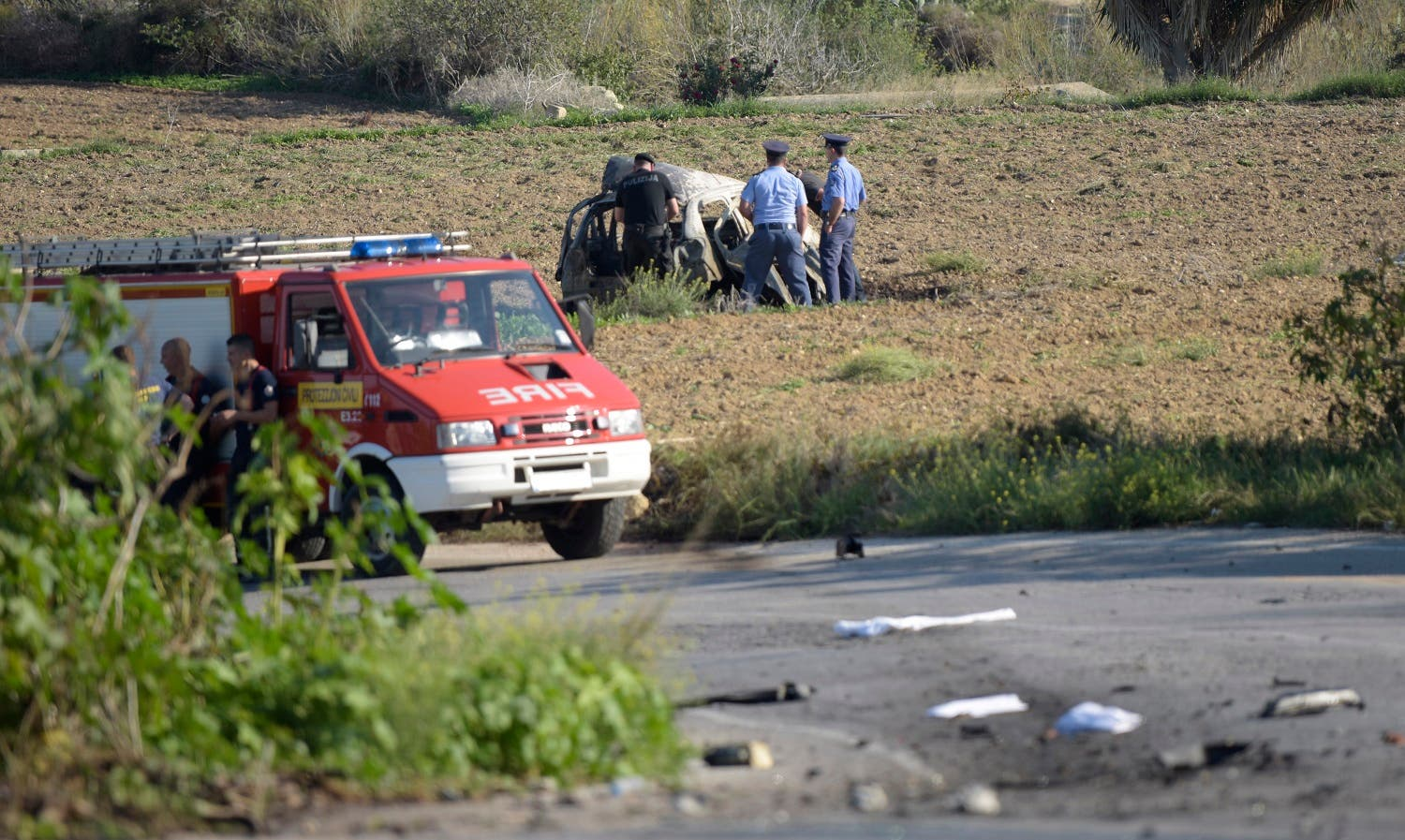 Police inspect the wreckage of a car bomb believed to have killed journalist and blogger Daphne Caruana Galizia close to her home in Bidnija, Malta? on October 16, 2017. The force of the blast broke her car into several pieces and catapulted the journalist's body into a nearby field, witnesses said. She leaves a husband and three sons. Caruana Galizia's death comes four months after Prime Minister Joseph Muscat's Labour Party won a resounding victory in a general election he called early as a result of scandals to which Caruana Galizia's allegations were central. (AFP)