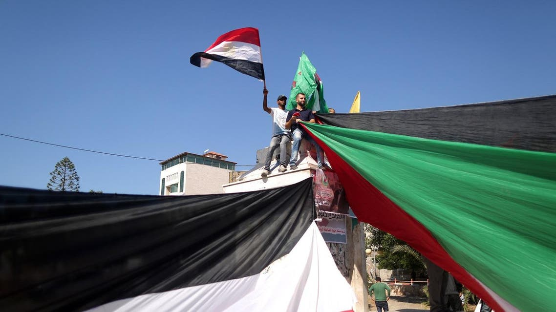 Palestinians wave the flags of Egypt and Palestine as they gather in Gaza City to celebrate after rival Palestinian factions Hamas and Fatah reached an agreement on ending a decade-long split following talks mediated by Egypt on October 12, 2017. Details of the agreement have not yet been released and a press conference was being planned in the Egyptian capital. (AFP)
