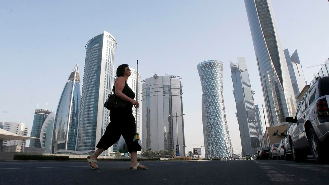 A woman crosses Al Wahda street hosting the Navigation Tower, headquarters of Qatargas (R), and Rasgas tower (2nd R) in Doha, April 8, 2013. (File photo: Reuters)