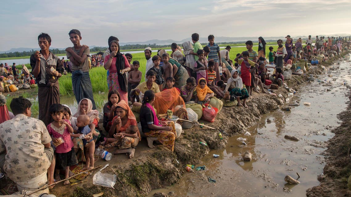 Newly arrived Rohingya Muslims, who crossed over from Myanmar into Bangladesh, rest on an embankment after spending a night in the open as they have been prevented from moving ahead towards refugee camps by Bangladesh border guard soldiers at Palong Khali, Bangladesh, Tuesday, Oct. 17, 2017. (AP)