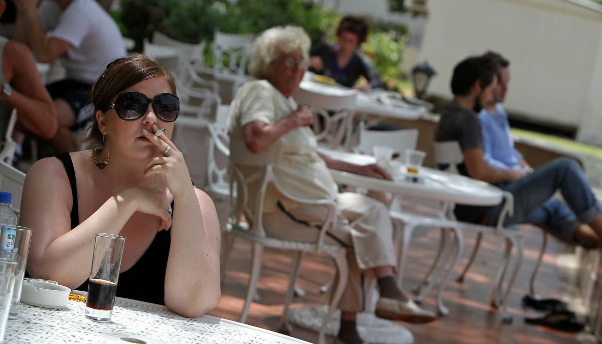 A passenger stranded in Dubai smokes a cigarette at a hotel in the Gulf emirate on April 19, 2010. (AFP)