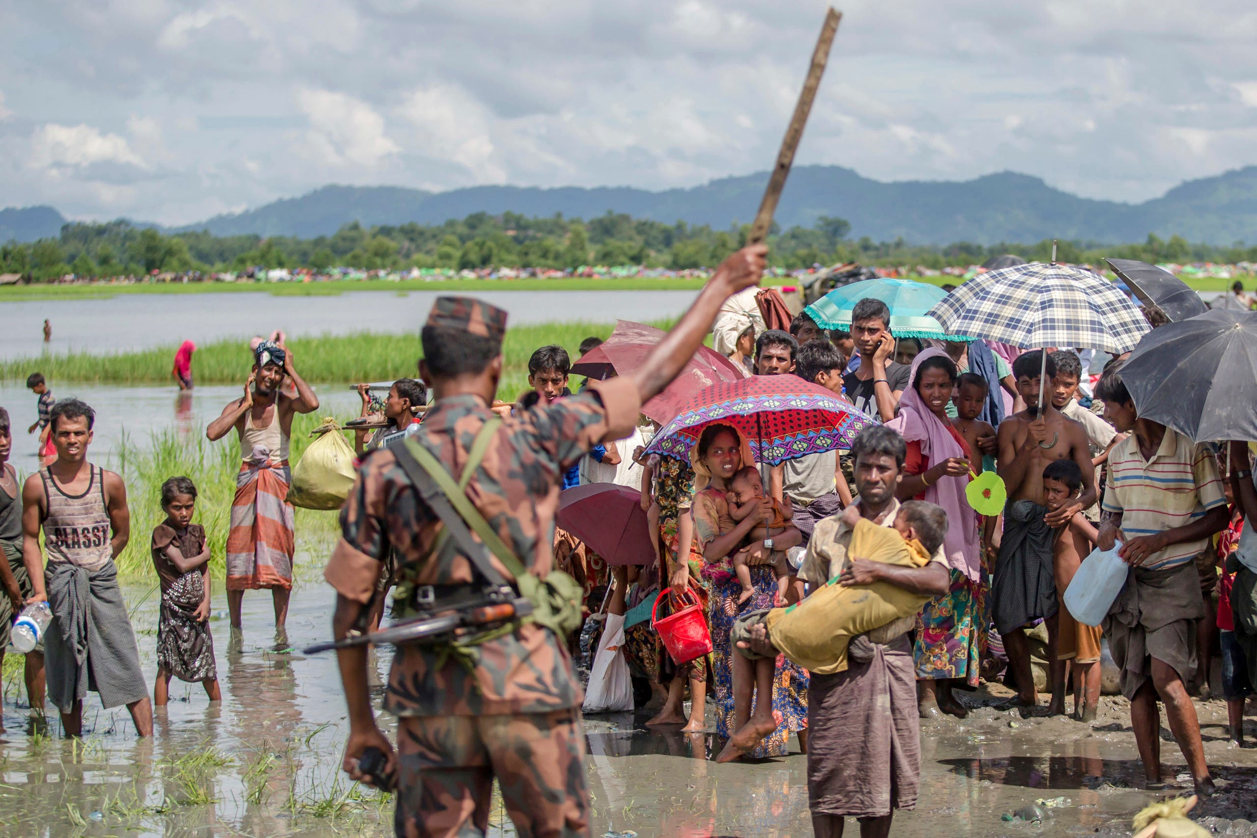A Bangladesh border guard soldier stops newly arrived Rohingya Muslims, who crossed over from Myanmar into Bangladesh, AP