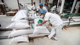 عمال ينقلون القمح