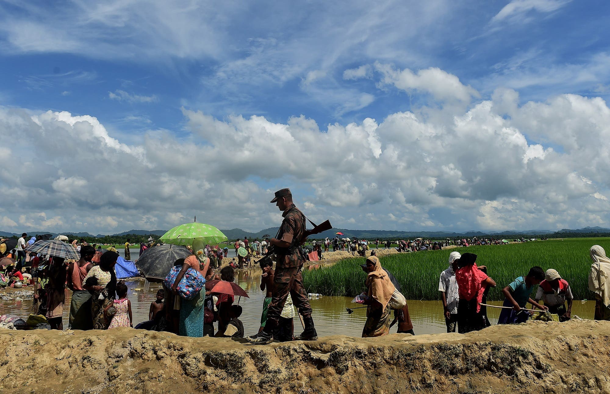 A Bangladesh border guard walks amongst Rohingya refugees walking in an area near no man's land on the Bangladesh side of the border with Myanmar after crossing the Naf River on October 17, 2017. (AFP)