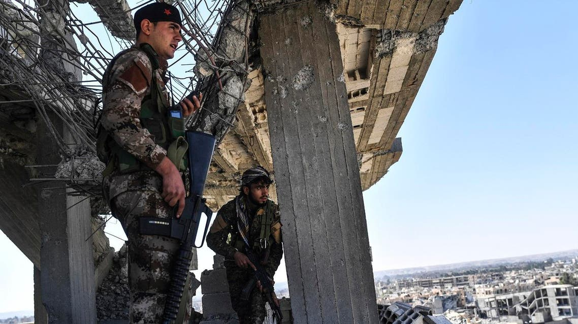 Members of the Syrian Democratic Forces (SDF), backed by US special forces, walk on a building near Raqa's central hospital as they clear the last positions on the frontline on October 16, 2017 in the Islamic State (IS) group jihadists crumbling stronghold. US-backed fighters battled hundreds of Islamic State group jihadists holed up in the last pockets of Syria's Raqa, as the former extremist stronghold stood on the verge of capture. (AFP)