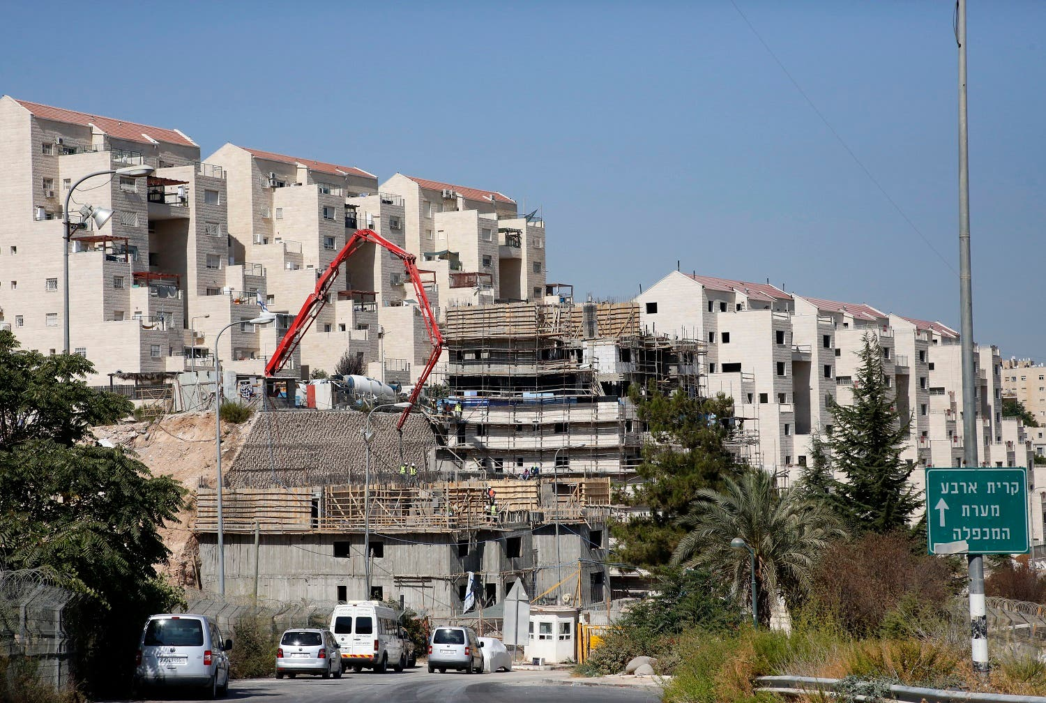 Construction workers building new houses in the Israeli settlment of Kiryat Arba, east the West Bank town of Hebron. (File photo: AFP)