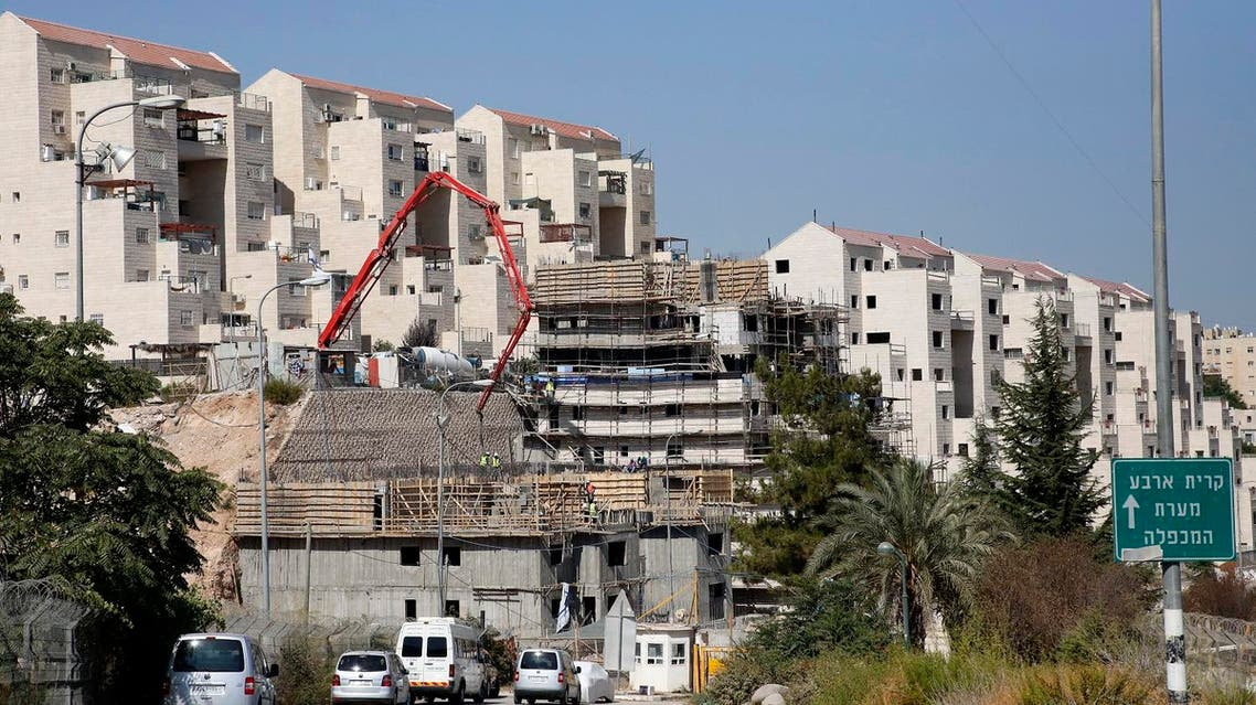 (FILES) This file photo taken on August 24, 2017 shows construction workers building new houses in the Israeli settlment of Kiryat Arba, east the West Bank town of Hebron. Israeli authorities on October 16, 2017 approved permits for 31 settler homes in Hebron in the occupied West Bank, the first such approvals for the flashpoint city since 2002, the Peace Now NGO said. (AFP)