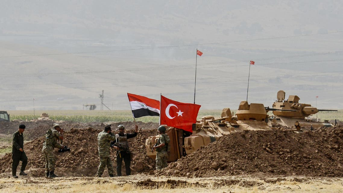 A photographer takes pictures as soldiers stand next to tanks bearing Turkish and Iraqi flags during a joint military exercise near the Turkish-Iraqi border at Silopi district in Sirnak on September 26, 2017. AFP