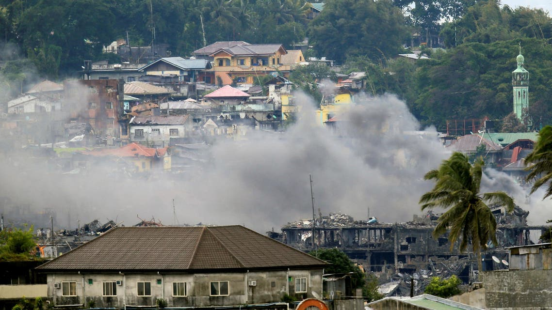 A smoke billows on damaged houses and buildings as the government troops continue their assault against the pro-Islamic State militant group during a clearing operations in Marawi city, southern Philippines, October 18, 2017. (Reuters)
