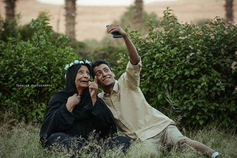 Egyptioan grandmother wearing a crown of flowers with her grandson.