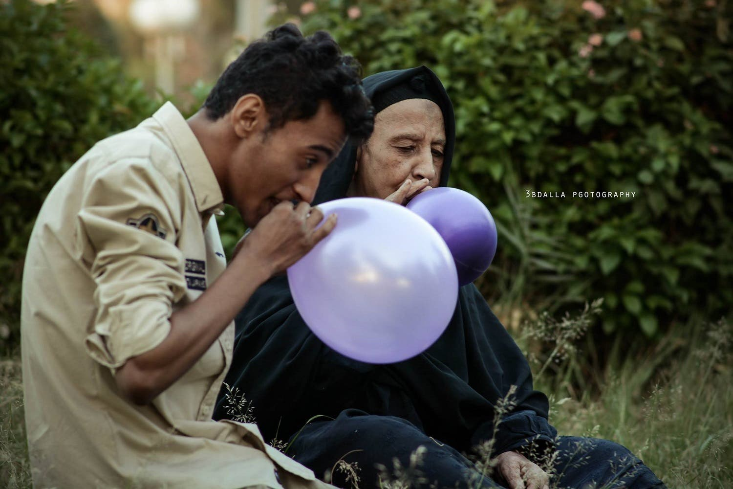 Egyptian grandson and grandmother blowing balloons together.