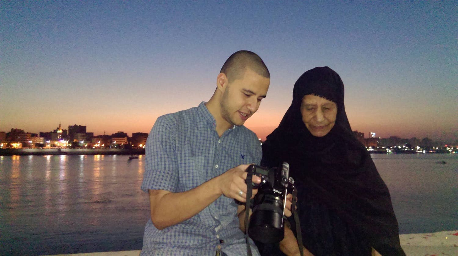 Abdullah Mohammad, the photographer, showing the digital images from the photoshoot to the grandmother.
