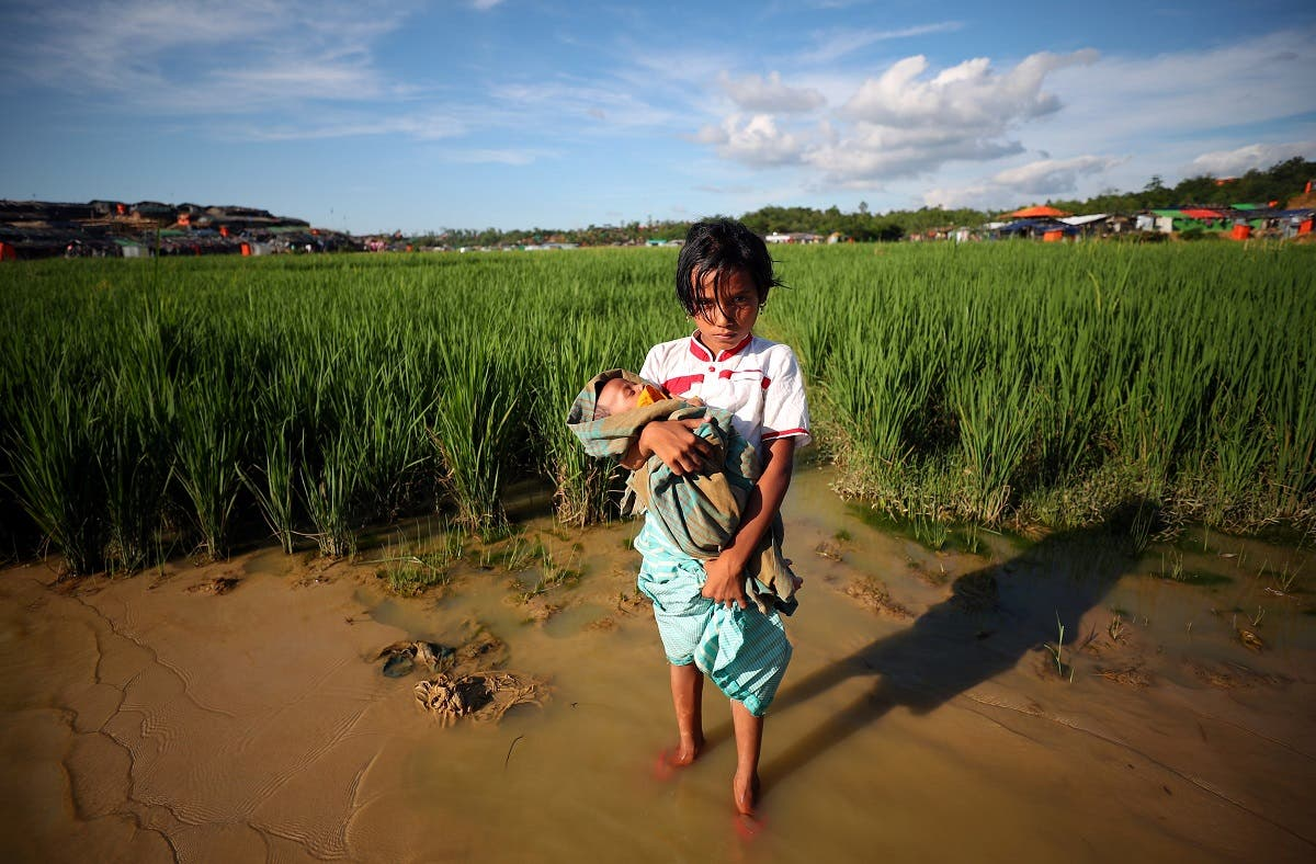 Somima, an 8 year old Rohingya refugee carries her 3-month old sister Alina through Palong Khali refugees camp near Cox's Bazar. (Reuters)