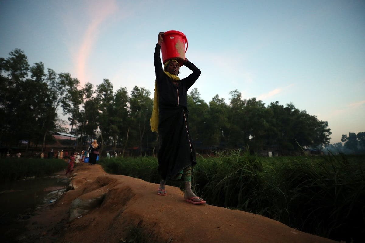 A Rohingya refugee carries supplies through Kutupalong refugees camp near Cox's Bazar. (Reuters)