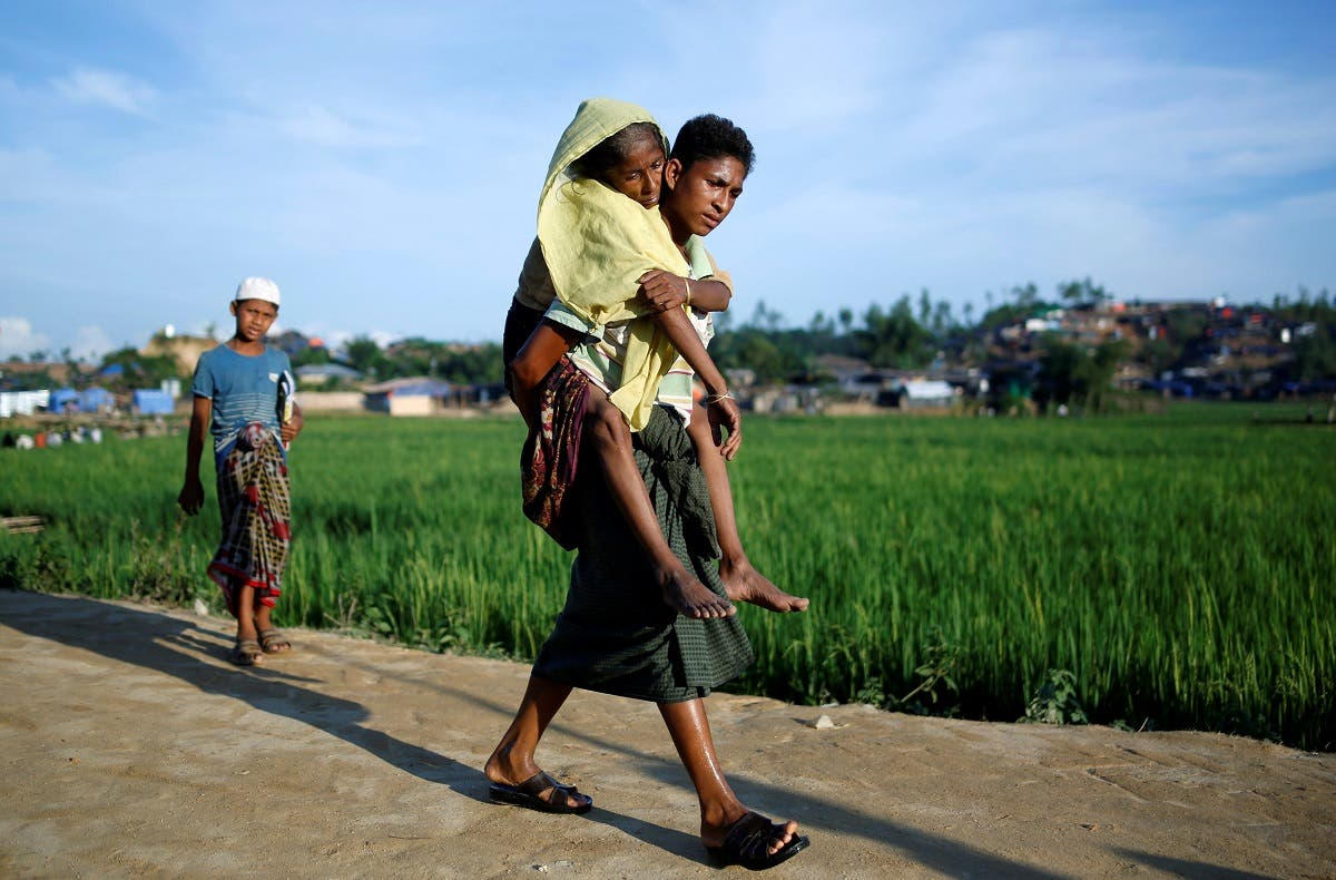 A Rohingya refugee carries his mother on his back at a refugee camp in Palong Khali. (Reuters)
