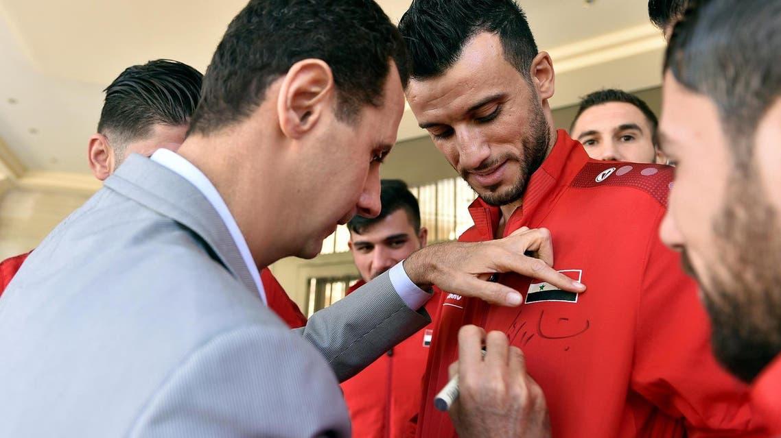 Assad autographs shirts of Syria's national football team