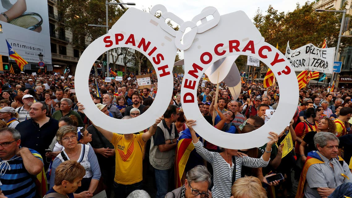 People hold a giant pair of handcuffs during a demonstration organised by Catalan pro-independence movements ANC (Catalan National Assembly) and Omnium Cutural, following the imprisonment of their two leaders Jordi Sanchez and Jordi Cuixart, in Barcelona, Spain October 21, 2017. (Reuters)