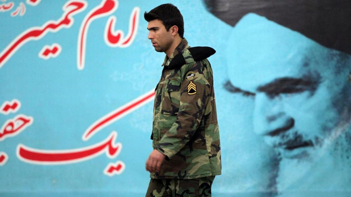 A member of Iran's Revolutionary Guards elite unit walks past a giant poster featuring the founder of Iran's Islamic Republic, Ayatollah Ruhollah Khomeini. (AFP)