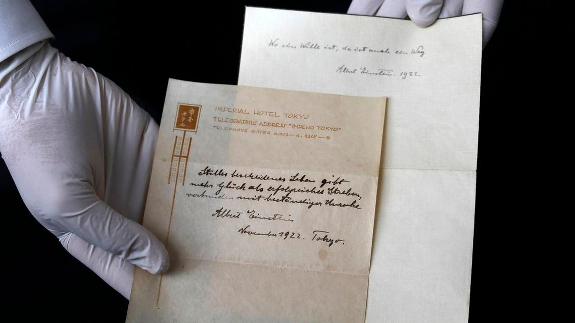 A picture taken on October 19, 2017, shows Gal Wiener, owner and manager of the Winner's auction house in Jerusalem, displays two notes written by Albert Einstein, in 1922, on hotel stationary from the Imperial Hotel in Tokyo Japan. A note that Albert Einstein gave to a courier in Tokyo, briefly describing his theory on happy living, has surfaced after 95 years and is up for auction in Jerusalem. (AFP)