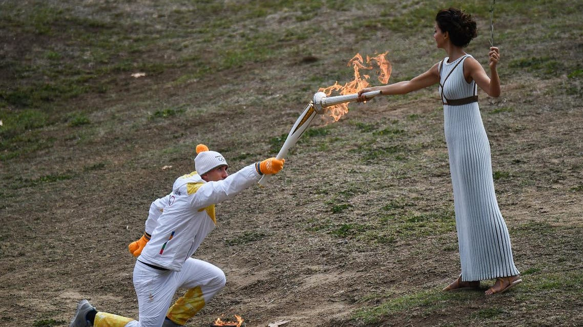 First Greek torchbearer for Pyeongchang 2018, cross-country skier Apostolos Angelis (L) lights the OLympic torch to take the first relay from the Olympic flame held by actress Katerina Lechou at the Temple of Hera on October 24, 2017 during the lighting ceremony of the Olympic flame for the 2018 Winter Olympics in Pyeongchang, South Korea. The 2018 Winter Olympics will take place from February 9 until February 25, 2017. (AFP)