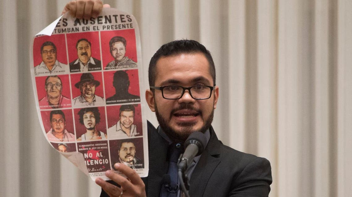 Marcos Vizcarra, a journalist for the Mexican publication Noroeste, holds up a poster with missing Mexican journalists as he speaks after receiving the 2017 Peter Mackler Award at the National Press Club in Washington, DC, October 26, 2017. (AFP)