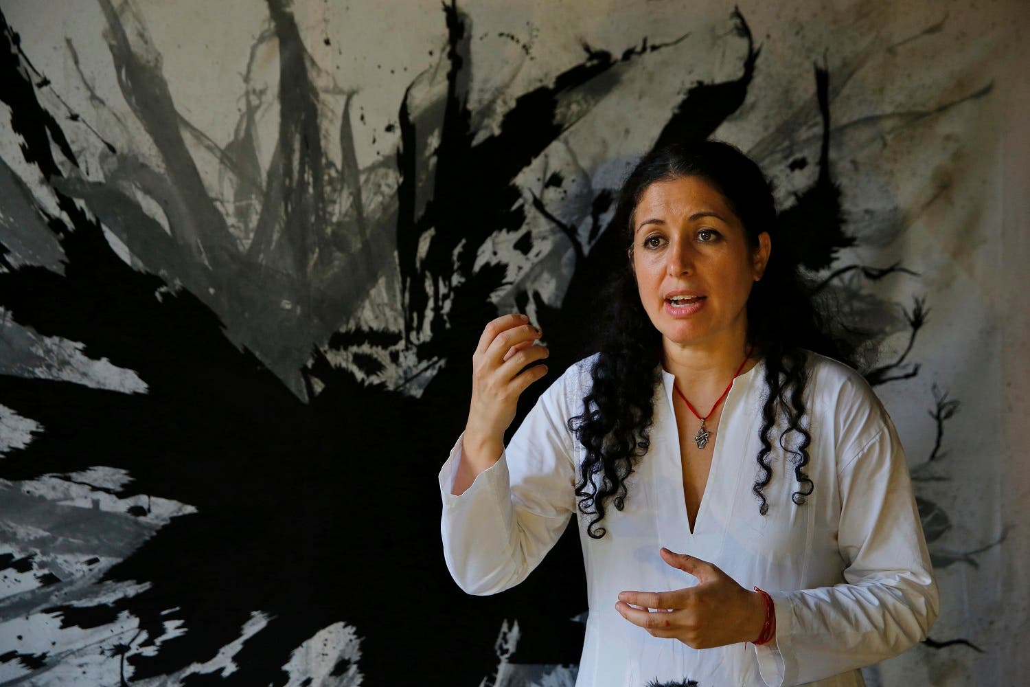 Lebanese artist Zena El Khalil speaks during an interview with The Associated Press, in front of one of her paintings in Beit Beirut, in Beirut, Lebanon. (AP)