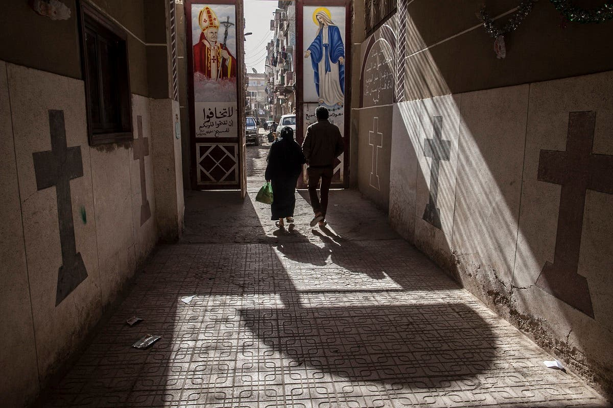 Coptic Christians walk outside St. Markos Church in Minya, south of Cairo, Egypt, where two policemen guarding the church were shot dead by unknown gunmen on the early hours of Tuesday, Jan. 6,. 2015, a day before Egypt's Coptic Christmas falls. (AP)