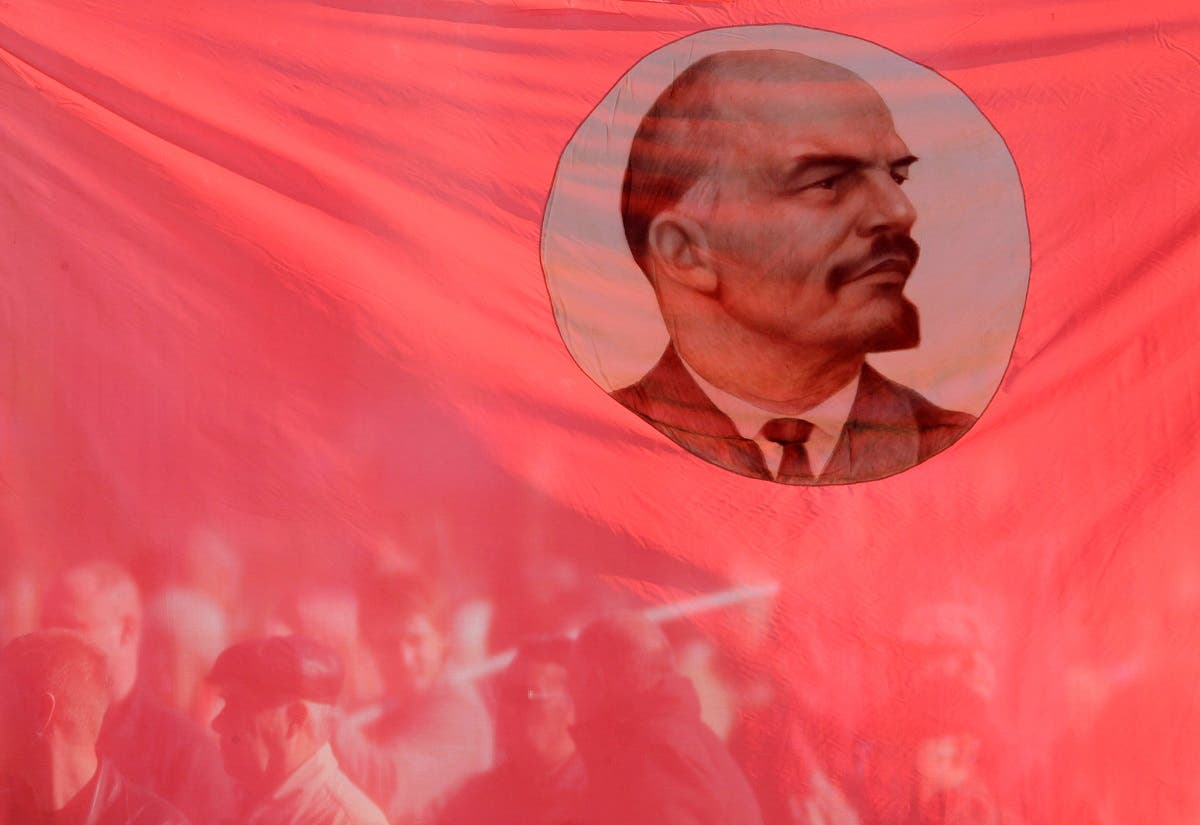 Russian communist supporters are seen through a flag, displaying an image of Soviet state founder Vladimir Lenin. (Reuters)