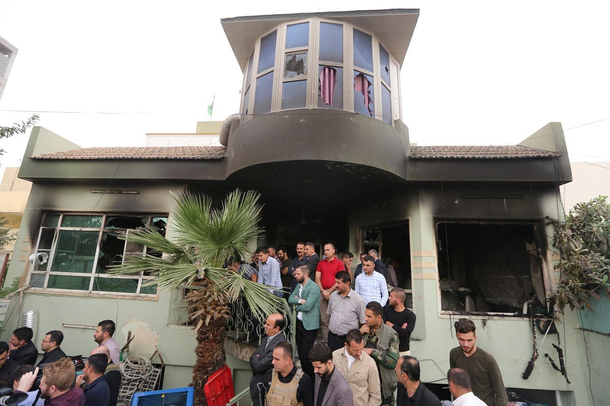 People gather at the Patriotic Union of Kurdistan (PUK) building after it was burnt overnight, in the town of Zakho. (Reuters)
