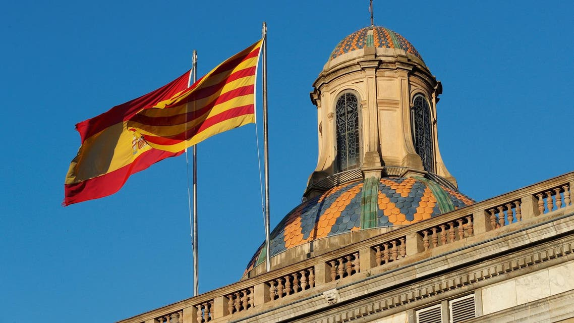 Spanish and Catalan flags flutters atop the Catalan regional government headquarters. (Reuters)