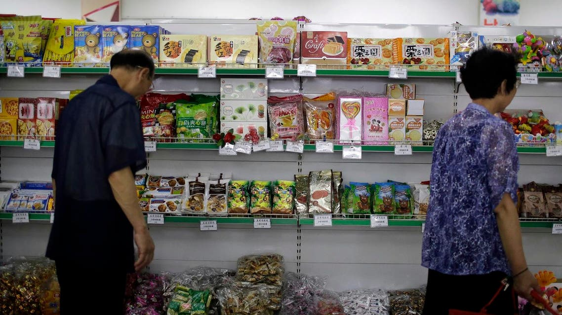 People walk past a shelf displaying both local and imported snacks from China at the Potonggang department store in Pyongyang, North Korea. (AP)