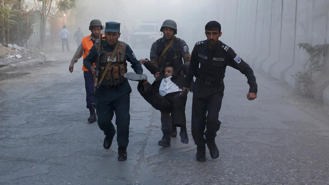 Afghan policemen carry an injuried after a blast in Kabul, Afghanistan. (Reuters)