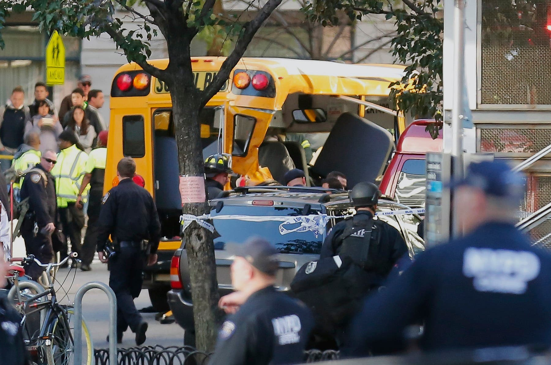 Authorities respond near a damaged school bus where a terror suspect drove onto a busy bicycle path near the World Trade Center memorial and struck several people. (AP)