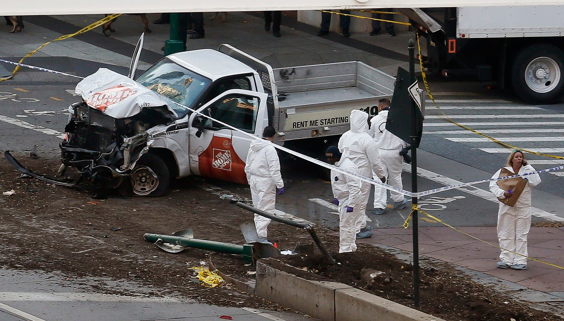 Authorities stand near a damaged Home Depot truck after a motorist drove onto a bike path near the World Trade Center memorial, striking and killing several people Tuesday. (AP)