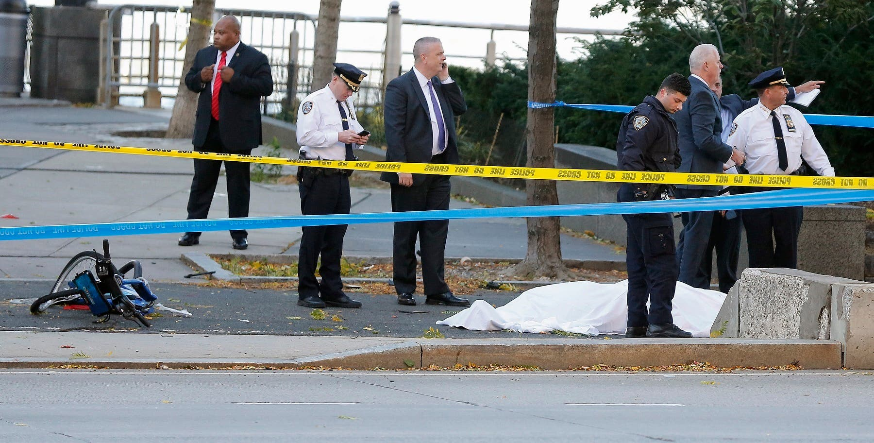 Authorities investigate the scene around a body covered under a white sheet next to a mangled bike along the bike path in New York. (AP)