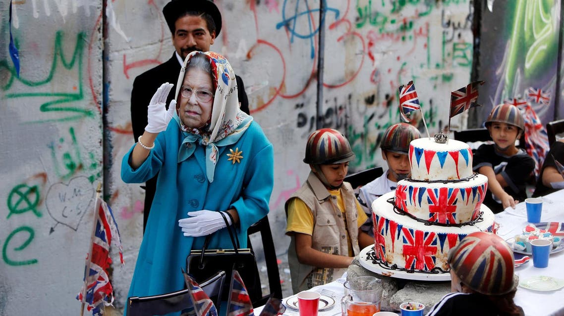 A person, dressed as Britain's Queen Elizabeth II, gestures during an event ahead of the anniversary of the Balfour Declaration, in Bethlehem on November 1, 2017. (Reuters)