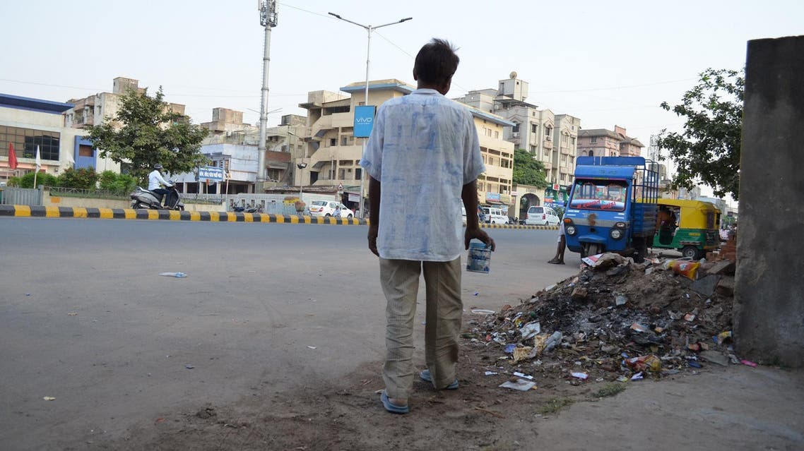 A man walks past a garbage dump on his way to a toilet. (Supplied)