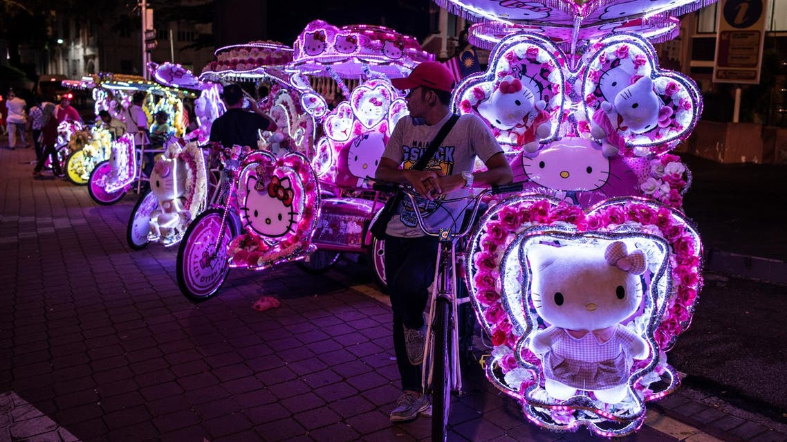 This picture taken on October 21, 2017 shows riders waiting for customers on trishaws with illuminated LED lights of Hello Kitty decorations on a street in Malacca. (AFP)