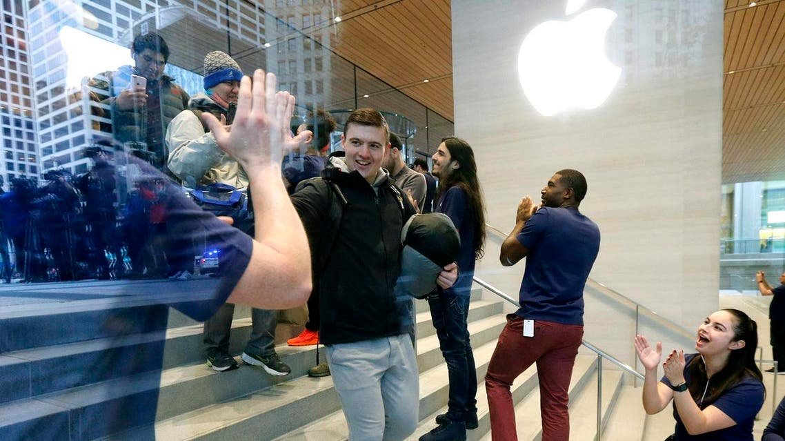 Chase Thilleman receives a high five from an Apple employee as he is first in line to buy the Apple iPhone X at the new Apple Michigan Avenue store along the Chicago River Friday, Nov. 3, 2017.