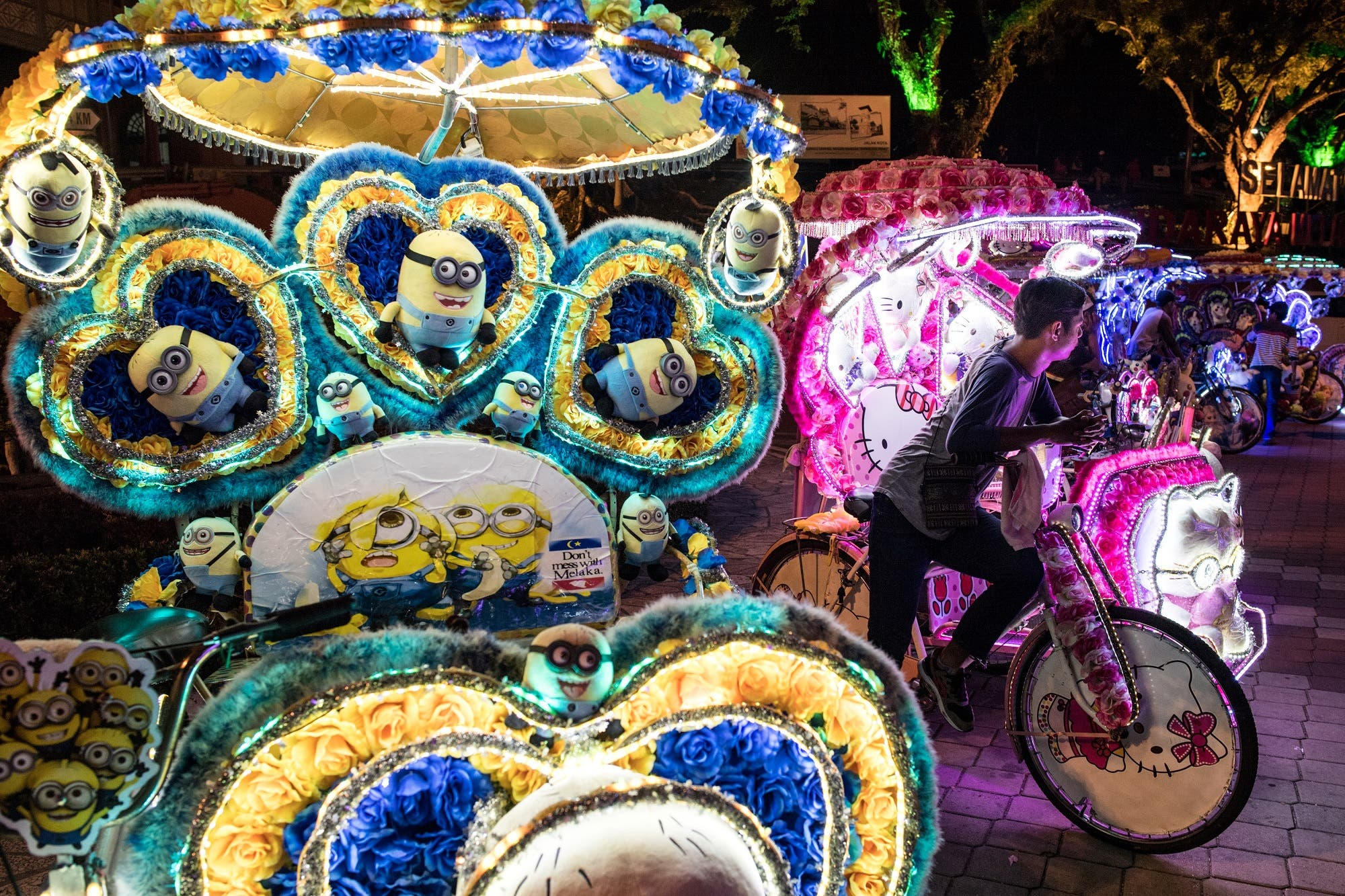 This picture taken on October 21, 2017 shows trishaws decorated with Minions (L) and Hello Kitty (R) characters and LED lights on a street in Malacca. (AFP)